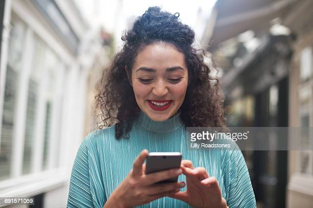 Young woman texting in lane of shops