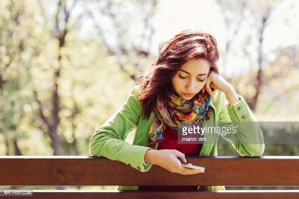 Young woman texting in the park