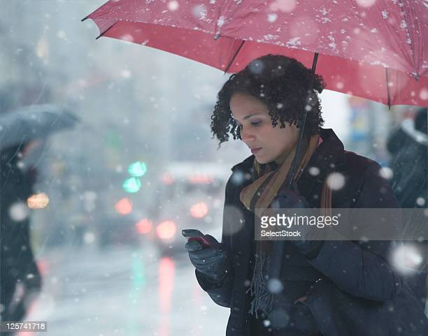 Young woman texting in the snow
