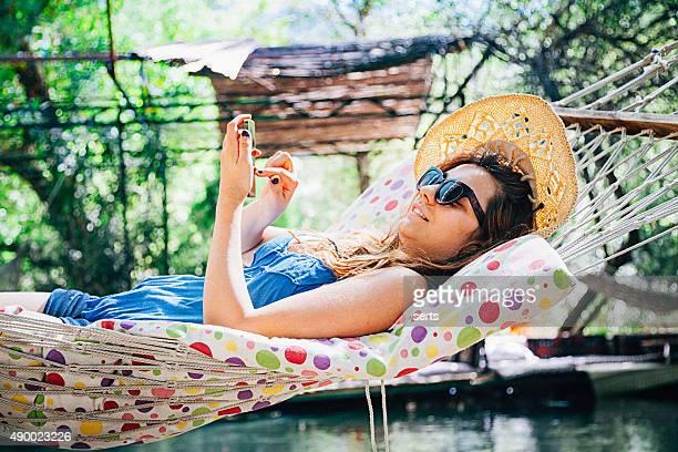 Giovane donna messaggi di testo messaggio su un'amaca
