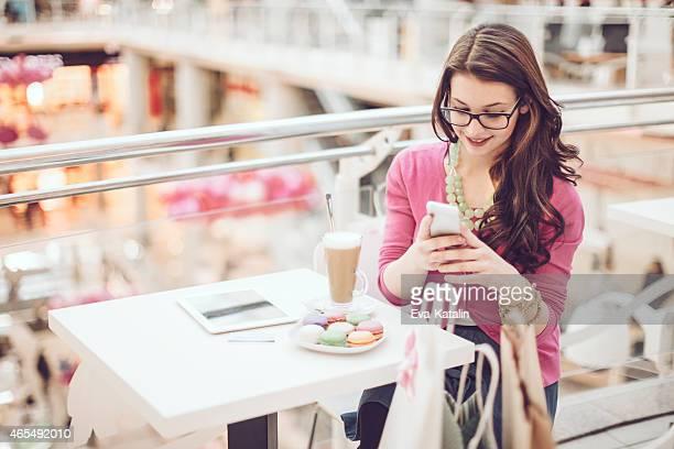 Joven mujer enviando mensajes de texto en su teléfono móvil en un centro comercial