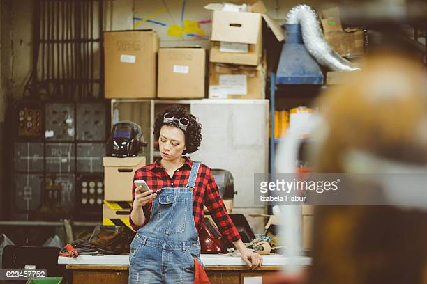 Young woman texting on phone in a workshop