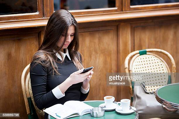 Young Woman Texting On Smartphone In A Sidewalk Cafeteria