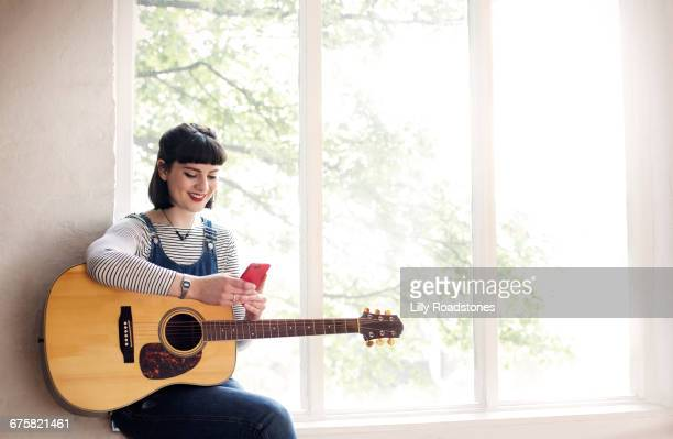 Young woman texting while holding guitar