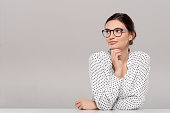 Beautiful young businesswoman wearing glasses and thinking with hand on chin. Smiling pensive woman with eyeglasses looking away isolated on grey background. Fashion and contemplative girl smiling and