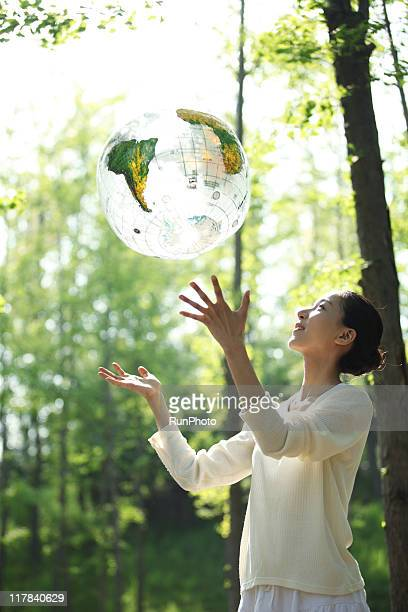 young woman throwing a globe ball in nature