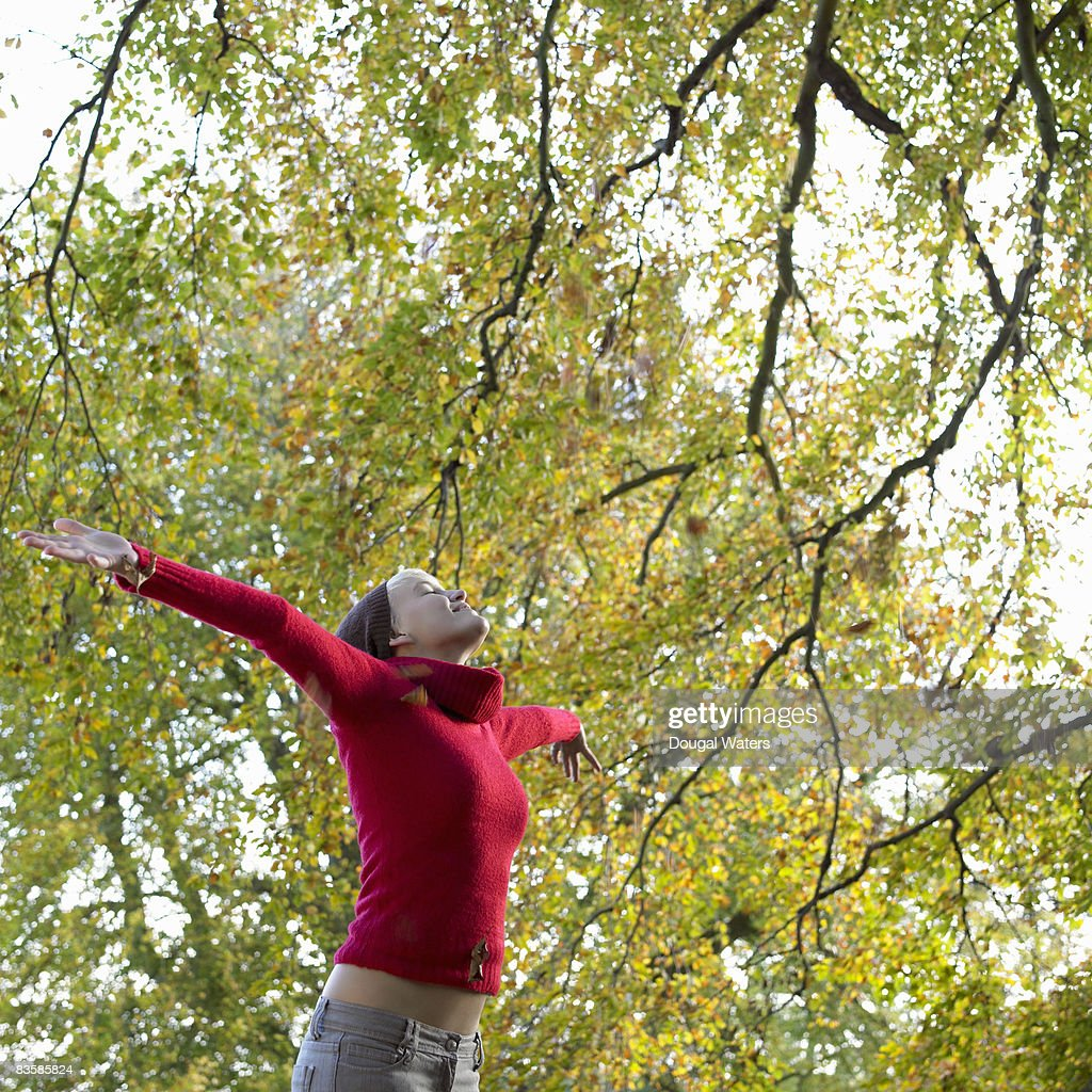 Young woman throwing autumn leaves in air. : Stock Photo
