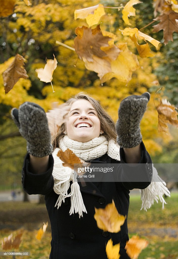 Young woman throwing autumn leaves in air, smiling : Stock Photo