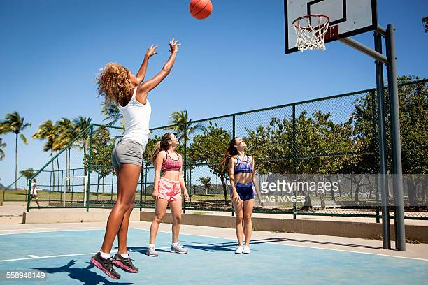 Young woman throwing basketball towards hoop while friends watch on