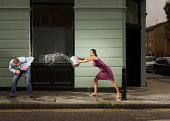 Young woman throwing bucket of water over man, outdoors