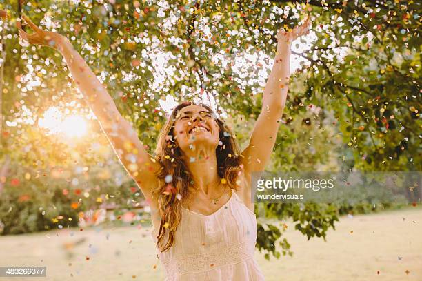 Young Woman throwing confetti in the park