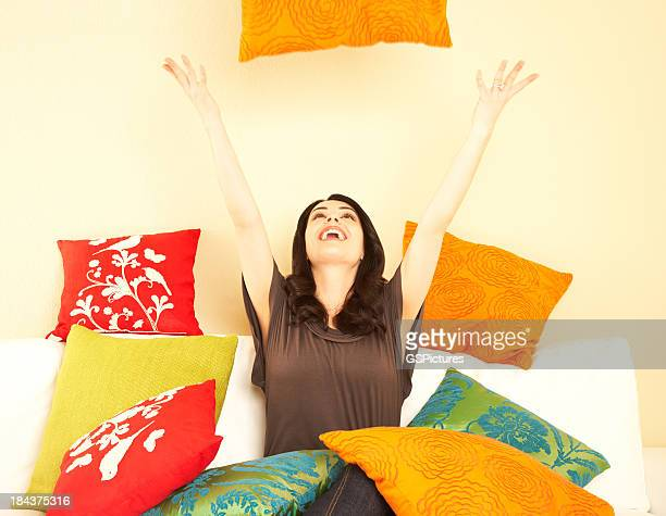 Young woman throwing pillows in living room