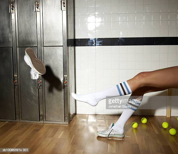 Young woman throwing shoes in locker room