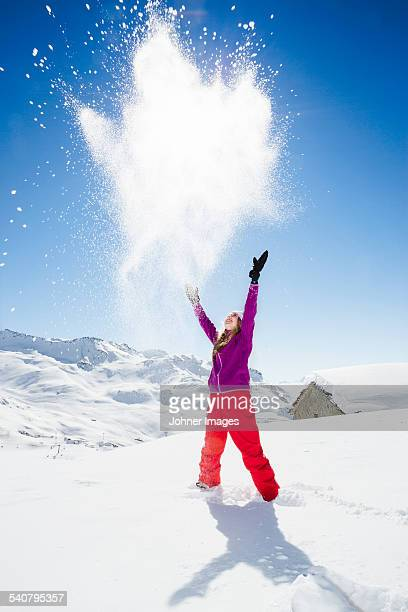 Young woman throwing snow