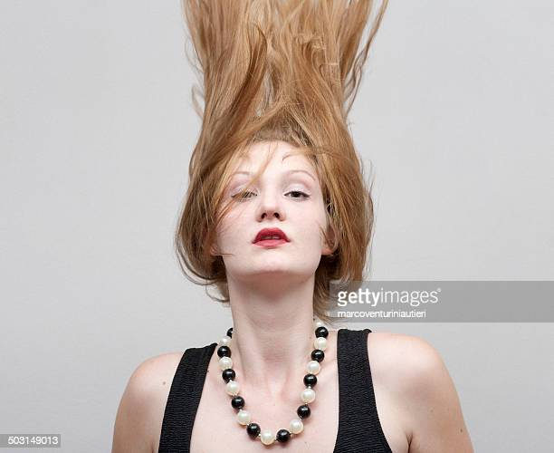 Young woman throws her hair up