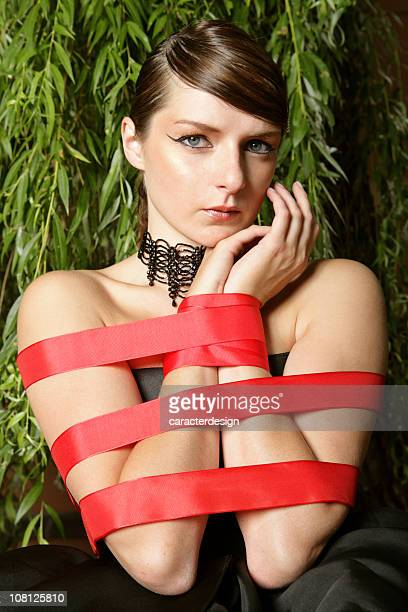 Young Woman Tied Up and Restrained with Red Tape