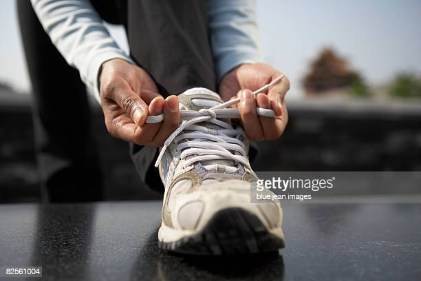 A young woman ties shoes during a work out, Chinese architectural element behind.