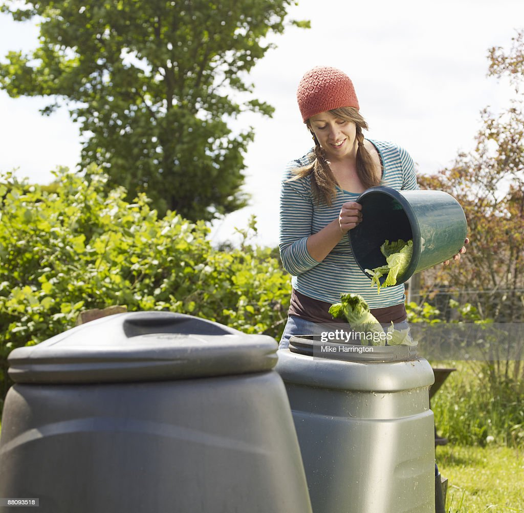 Young woman tipping cabbage leaves in compost bin : Stock Photo