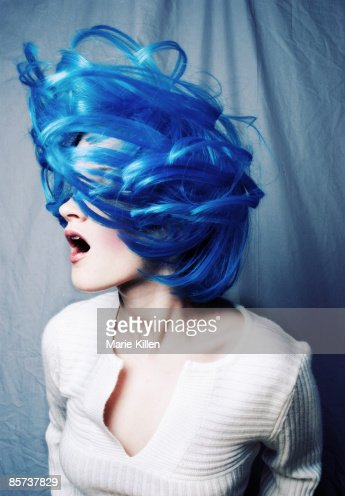 Young woman tossing blue hair, mouth open