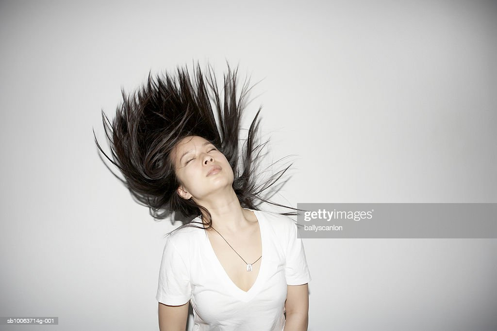 Young woman tossing hair, eyes closed : Stock Photo