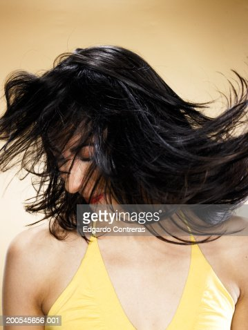 Young woman tossing hair, head and shoulders : Stock Photo