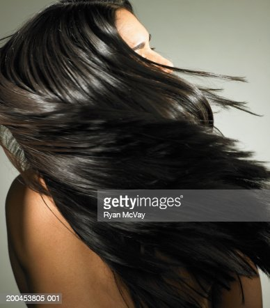 Young woman tossing hair, rear view : Stock Photo