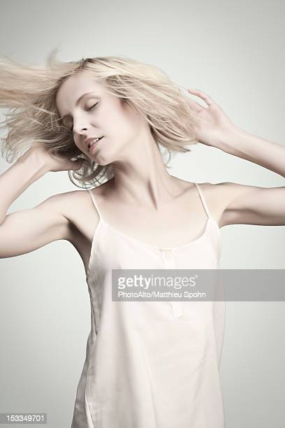 Young woman tossing hair with eyes closed, portrait