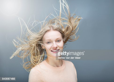 young woman tossing her  flowing long hair