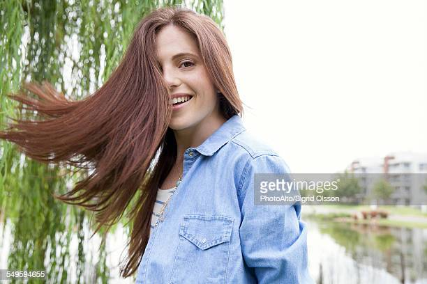 Young woman tossing her hair outdoors
