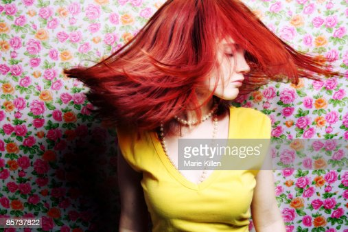Young woman tossing red hair, flower wallpaper