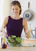 Young woman tossing salad, smiling