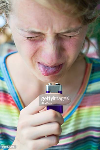 Young woman touching a battery with her tongue