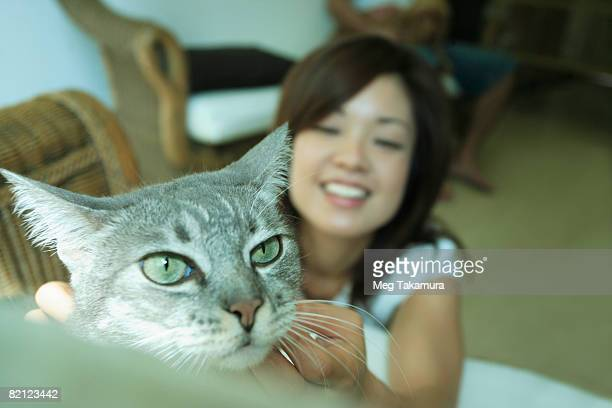 Young woman touching a cat's neck and smiling
