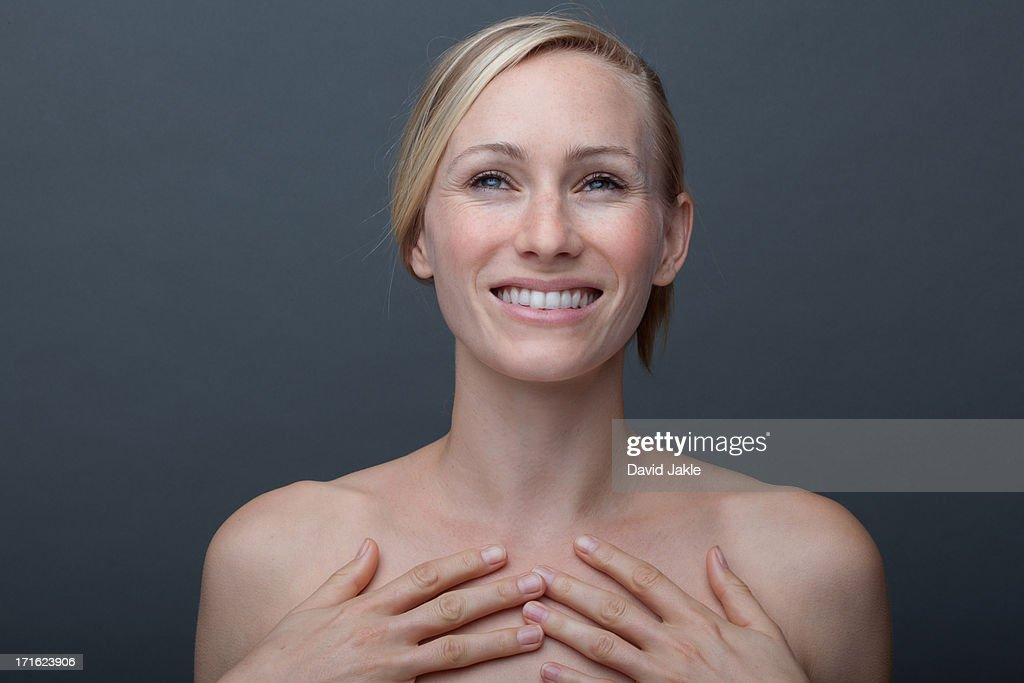Young woman touching chest : Stock Photo