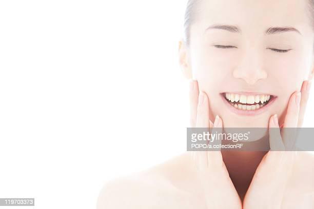 Young woman touching face
