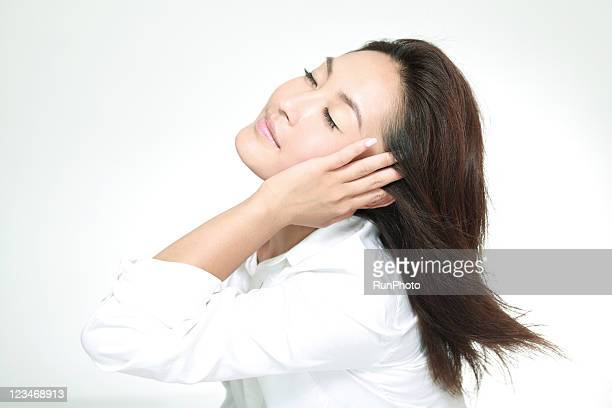 young woman touching hair with her eyes closed