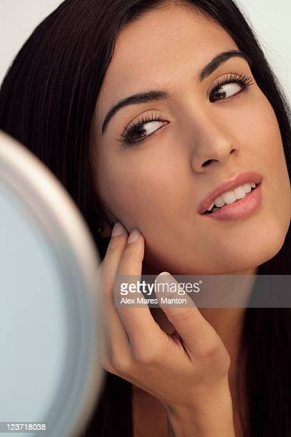 Young woman touching her face while looking at mirror.