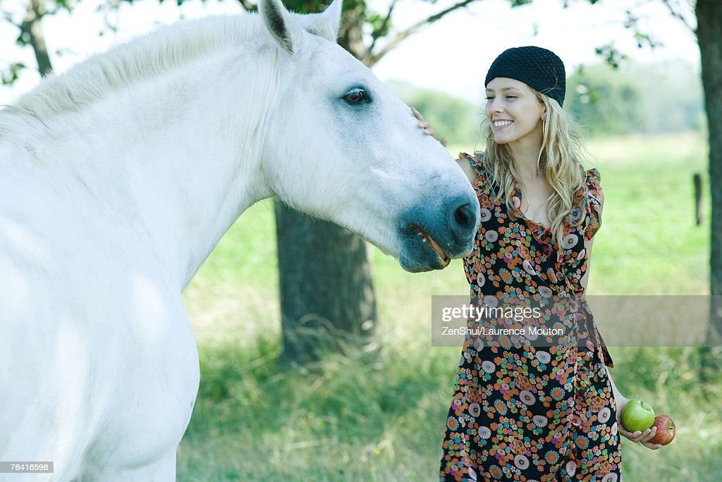 Young woman touching horse, holding apples : Stock Photo