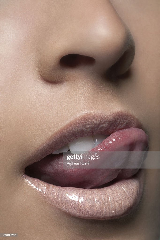 Young woman touching lip with tongue, close up.