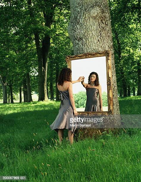 Young woman touching reflection in mirror hung on tree