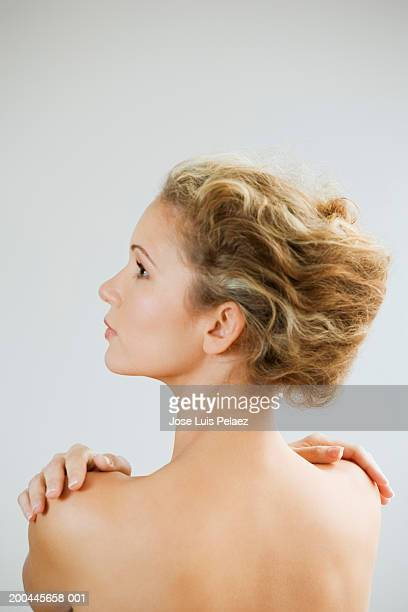Young woman touching shoulders, looking to side, rear view, close-up