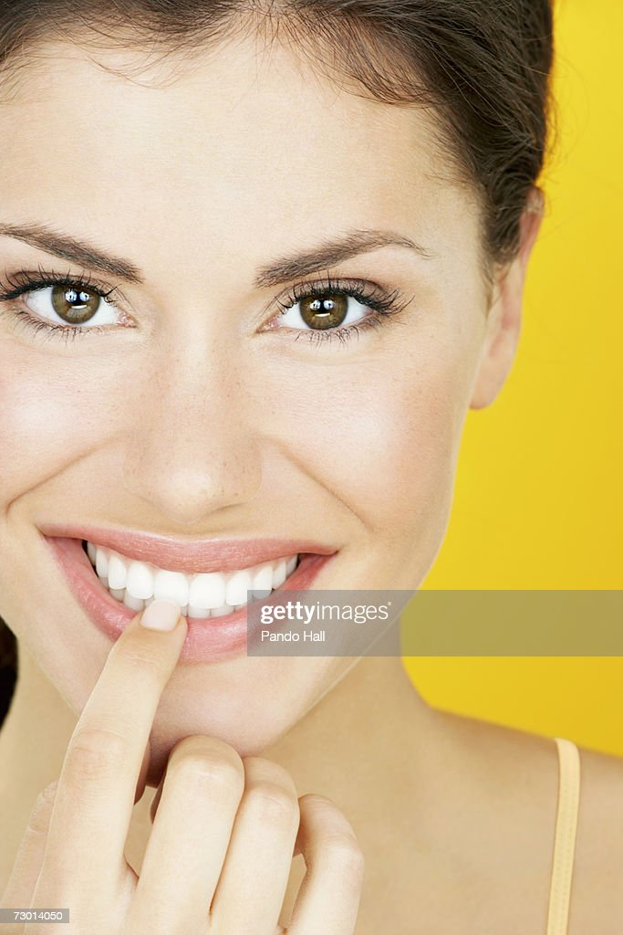 Young woman touching teeth, close-up, portrait : Stock Photo