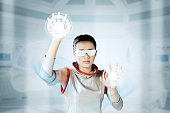 Image of young woman wearing futuristic glasses while touching two buttons on the virtual screen