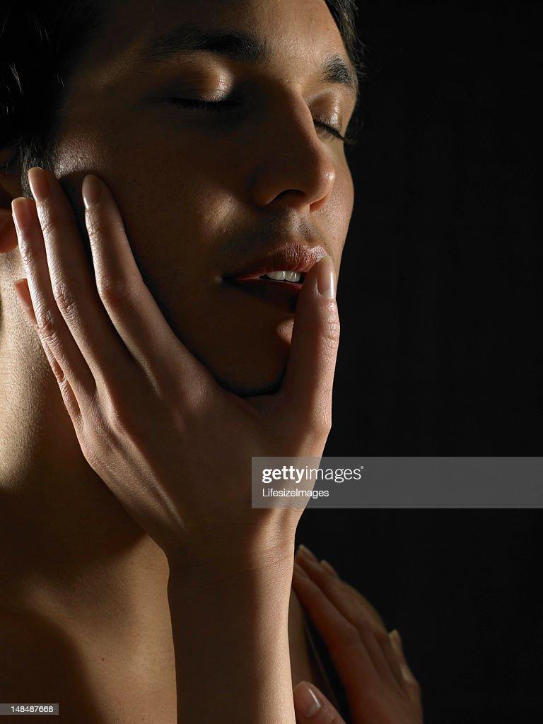 Young woman touching young man's cheek, running thumb across lip : Stock Photo