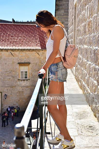 Young woman tourist overlooking old town Dubrovnik from wall,