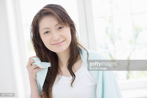 Young woman towel-drying hair