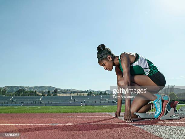 Young woman track athlete at starting block
