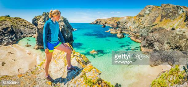 Young woman trail runner overlooking idyllic beach ocean bay panorama