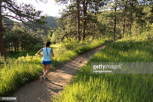 Young woman trail runs Bear Creek forest Colorado Rocky Mountains
