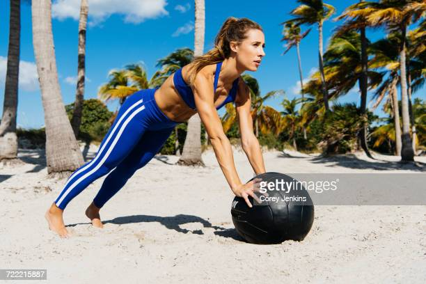 Young woman training, doing push ups on exercise ball at beach
